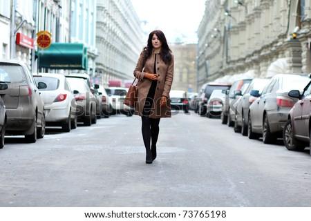 beautiful young woman walking on the street - stock photo
