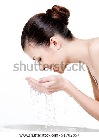Beautiful young woman washing her face - white background