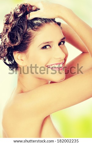 Beautiful  young woman washing her hair with shampoo - stock photo
