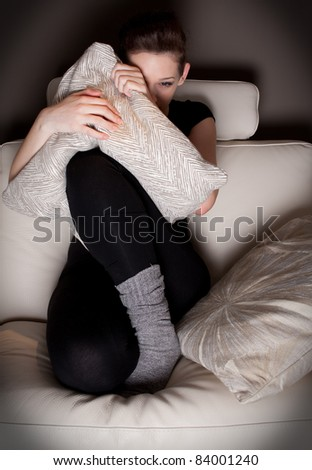 Beautiful young woman watching a horror movie alone - stock photo