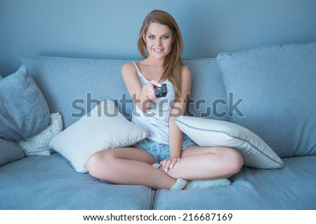 Beautiful young woman watching television sitting surrounded by cushions on a comfortable sofa with the remote control in her hand