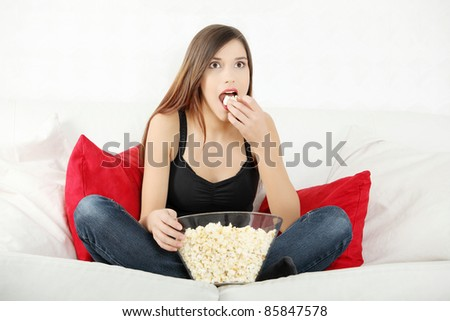 Beautiful young woman watching TV and eating popcorn