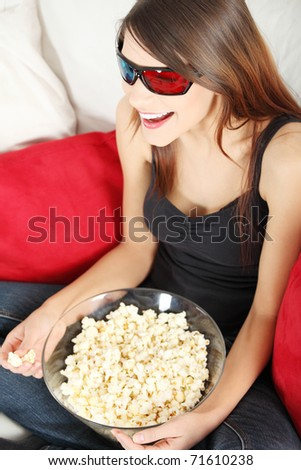 Beautiful young woman watching TV in 3d glasses and eating popcorn - stock photo