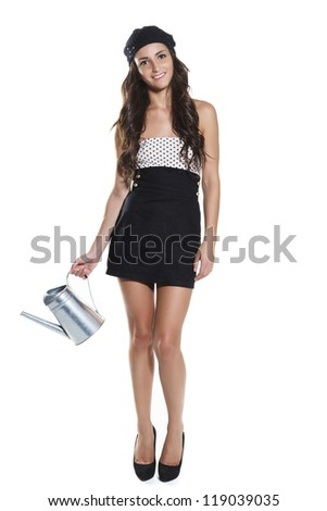 Beautiful young woman watering a plant, white background - stock photo