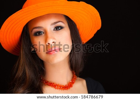Beautiful young woman wearing a colorful hat on a black background. - stock photo