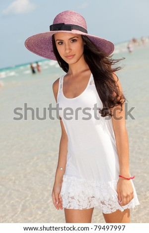 Beautiful young woman wearing a fancy purple hat and enjoying the pristine crystal clear shoreline of Miami's beautiful South Beach. - stock photo
