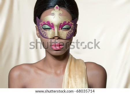 Beautiful young woman wearing a golden carnival mask, isolated on golden - stock photo