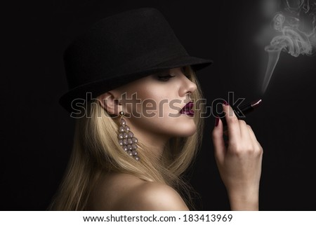 Beautiful young woman wearing a hat and holding a lipstick in hand, gangster style, with cigarette smoke - stock photo