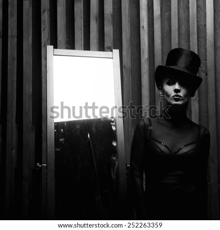 Beautiful young woman wearing a high hat near the mirror . Retro style - stock photo