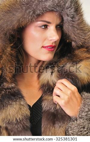 beautiful young woman wearing a luxurious fur coat with a hood - stock photo