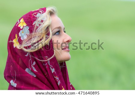 beautiful young woman wearing a maroon scarf in a green outdoor environment side view portrait