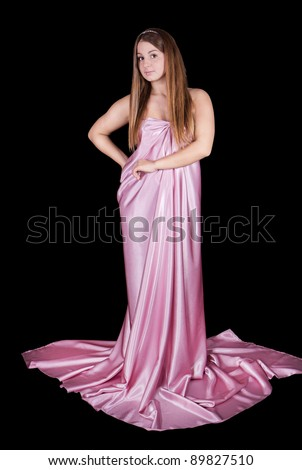 Beautiful young woman wearing a pink dress isolated on black background - stock photo