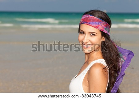 Beautiful young woman wearing a purple bandana enjoying the South Beach shoreline in Miami. - stock photo