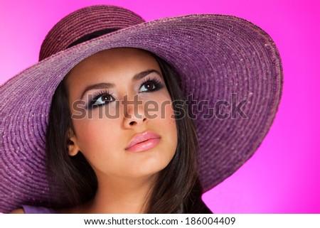 Beautiful young woman wearing a purple hat on a purple background. - stock photo