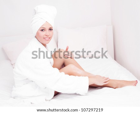 beautiful young woman wearing a towel and a white bathrobe and applying body lotion, in bed at home - stock photo
