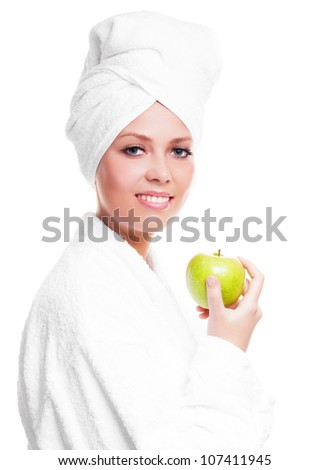 beautiful young woman wearing a towel and a white bathrobe and holding a green apple, isolated against white background - stock photo