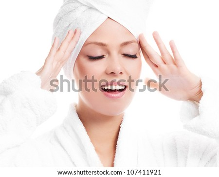 beautiful young woman wearing a towel and a white bathrobe  massaging her face, isolated against white background - stock photo