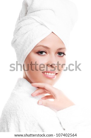 beautiful young woman wearing a towel and a white bathrobe touching her cheek, isolated against white background