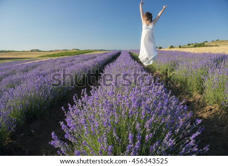 Beautiful young woman wearing a white dress jumping with joy in the middle of a lavender field in bloom. - stock photo