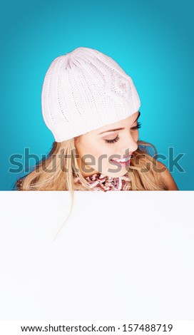 Beautiful young woman wearing a white knitted cap holding a blank white sign and looking down at it with a delightful smile