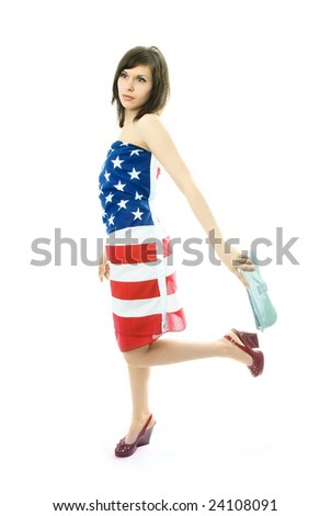 beautiful young woman wearing an American flag walks with a bag in her hand - stock photo