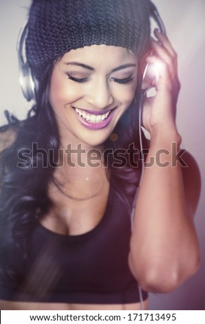 Beautiful young woman wearing beanie hat headphones happy listening to the beat of music - stock photo
