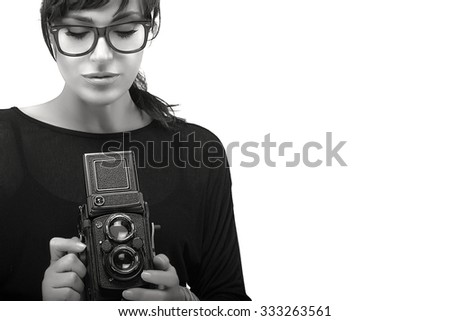 Beautiful Young Woman Wearing Black Clothes with Glasses Capturing Photo Using Vintage Camera. Black and White Portrait Isolated on White Background with Copy Space - stock photo