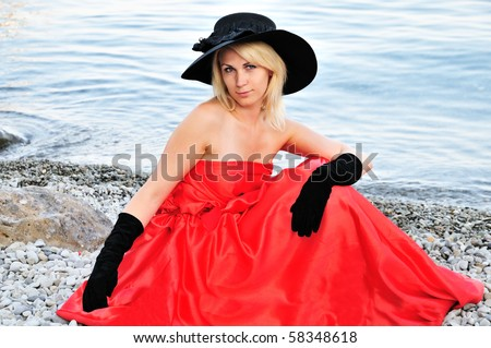 beautiful young woman wearing black hat, black gloves red dress is sitting on the beach near the sea