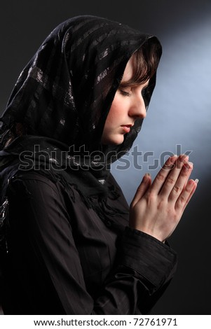 Beautiful young woman wearing black headscarf, eyes closed and hands together in prayer. - stock photo