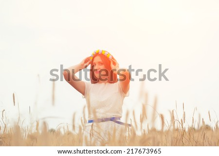 beautiful young woman wearing blue and yellow wreath and posing on wheat field - stock photo