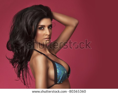 Beautiful young woman wearing blue bikini over pink background - stock photo
