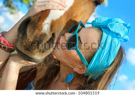 Beautiful young woman wearing blue dress with a horse outdoor. - stock photo