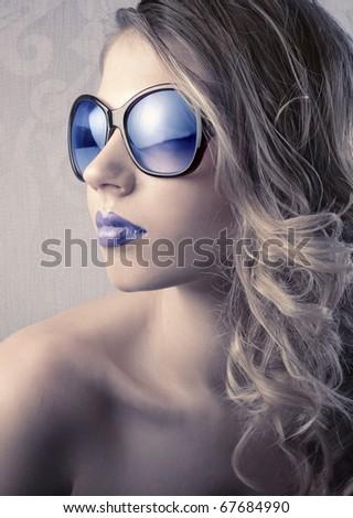 Beautiful young woman wearing blue sunglasses - stock photo