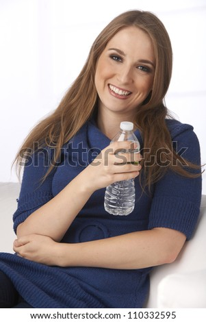 Beautiful young woman wearing blue sweater holding bottle of water at home on a sunny day. - stock photo