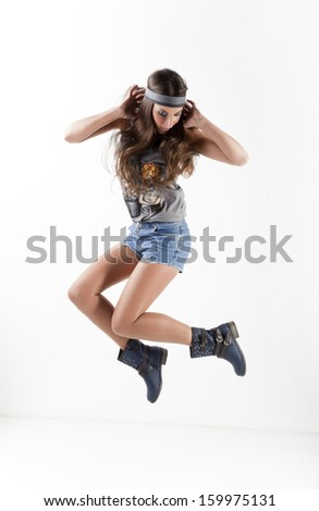 beautiful young woman wearing casual clothes and boots jumping - stock photo
