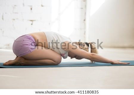 Beautiful young woman wearing casual clothing enjoying yoga indoors. Yogi girl working out in sunny loft interior. Doing Balasana, Child Pose, Ardha-Kurmasana (Half Tortoise Pose). Full length - stock photo