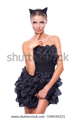 Beautiful young woman wearing cat ears and fashion black dress over white background - stock photo