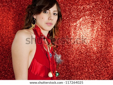 Beautiful young woman wearing Christmas tree decorations as a necklace while standing against a red glitter background.