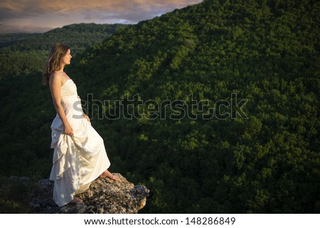 Beautiful young woman wearing elegant white dress standing on a rock overlooking mountains and green forests - stock photo