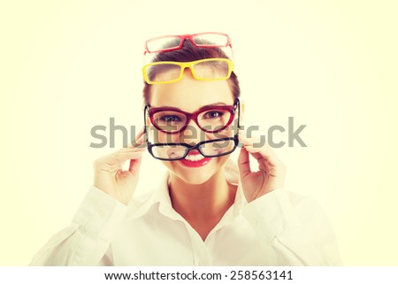 Beautiful young woman wearing four pair of glasses. - stock photo