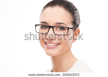 Beautiful young woman wearing glasses and smiling at camera - stock photo