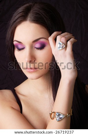 Beautiful young woman wearing golden ring and bracelet - stock photo