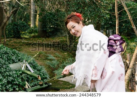 Beautiful young woman wearing japanese traditional kimono with bamboo fountain - stock photo