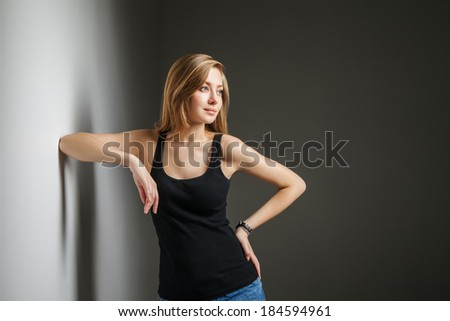 Beautiful young woman wearing jeans and black t-shirt over gray background - stock photo