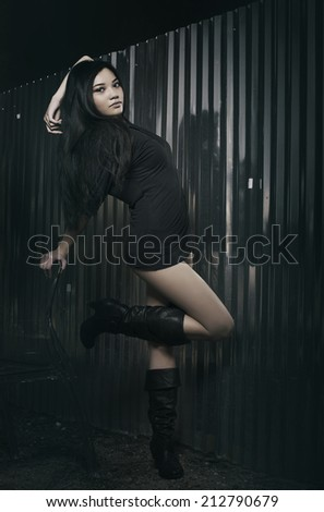 Beautiful young woman wearing little black dress and boots... Dark edgy sexy fashion shoot. - stock photo