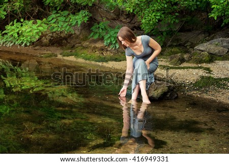 Beautiful young woman wearing long dress sitting on the rock with feet in a weedy pond water