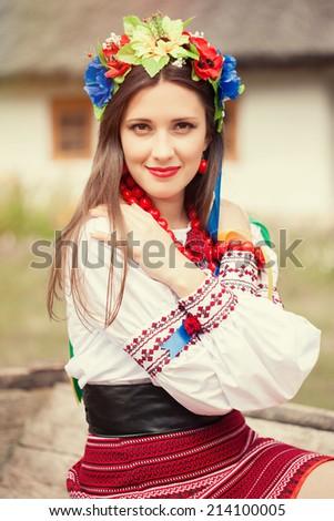 beautiful young woman wearing national ukrainian clothes posing near ukrainian hut - stock photo