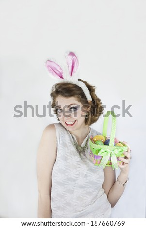 Beautiful young woman wearing rabbit ears and holding Easter basket with sequin Easter eggs.