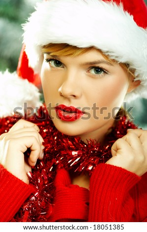 Beautiful young woman wearing santa hat next to christmas tree on white background