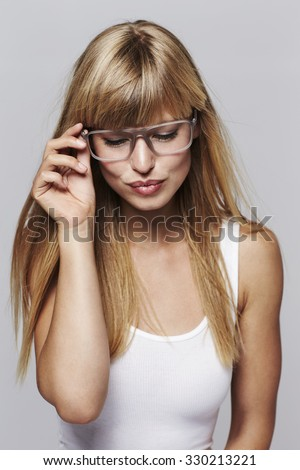 Beautiful young woman wearing spectacles, looking down